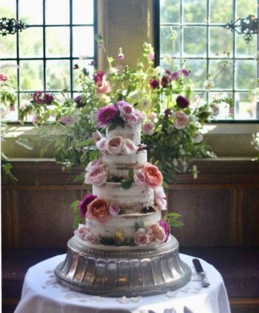 Beautiful semi-naked wedding cake at Rhinefield House. English flowers by Jenni Bloom