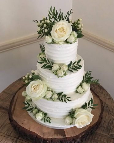 Buttercream coated wedding cake with fresh flowers at Careys Manor New Forest
