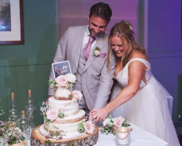 Lovely couple cutting their cake.