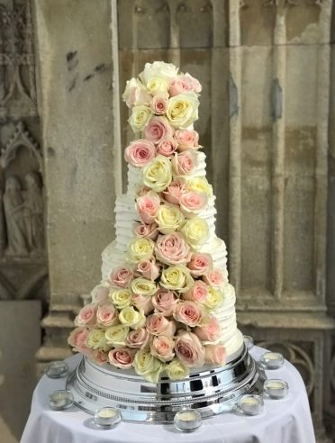Beautiful cascading fresh roses on a 5 tier buttercream coated wedding cake. At Highcliffe Castle flowers by Jukes florist.