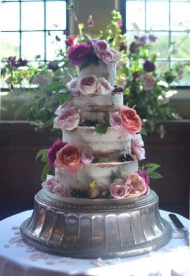 Semi-naked wedding cake at Rhinefield House. English flowers by Jenni Bloom