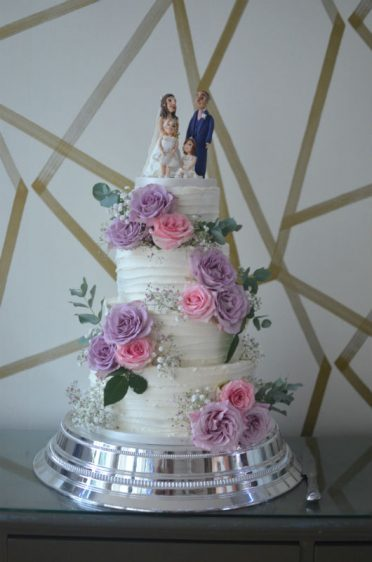 Four tier buttercream frosted wedding cake with handmade topper. At The Orchid Hotel