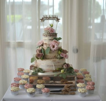 Semi-naked wedding cake with cupcakes. Flowers by Flowers by Design at Christchurch Harbour Hotel
