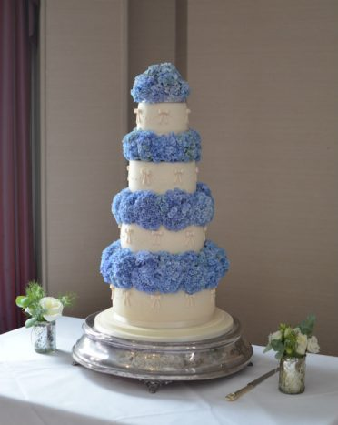 Ivory bows & blue hydrangea wedding cake. Flowers arranged by Liz Wyatt. Supplied by Penn Hill Flowers