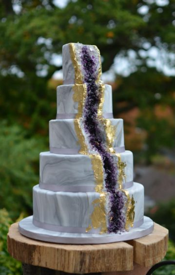 Geode amethyst crystal wedding cake with gold leaf.