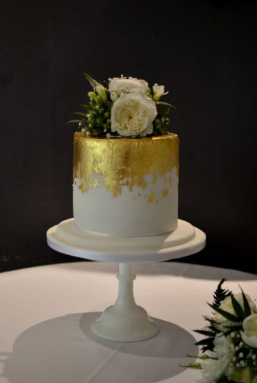 Tall gold leaf wedding cake at The Mill at Gordelton
