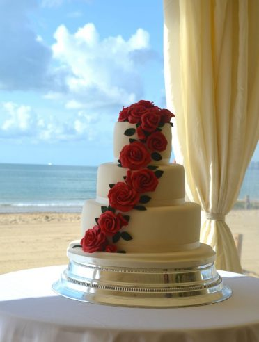 Bournemouth beach wedding cake with piano red roses.