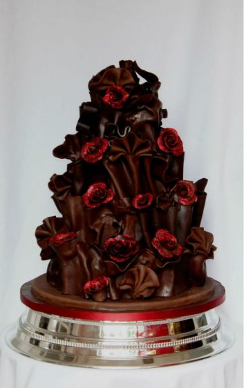 Chocolate wrapped wedding cake with red roses.