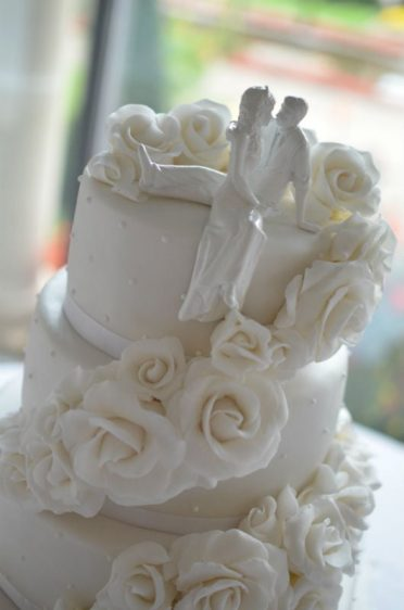 Close up of white roses wedding cake at Italian Villa.