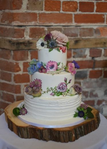 Hand painted wedding cake with fresh flowers at Highcliffe Castle.