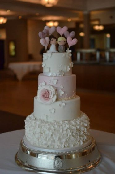 Four tier ruffles wedding cake with brides handmade topper at FJB Haven Hotel