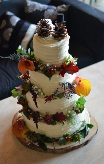 Buttercream frosted wedding cake with autumnal flowers.  At Kingston Country Courtyard.