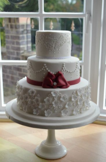 Lace & burgundy bow wedding cake delivered to Rhinefield House