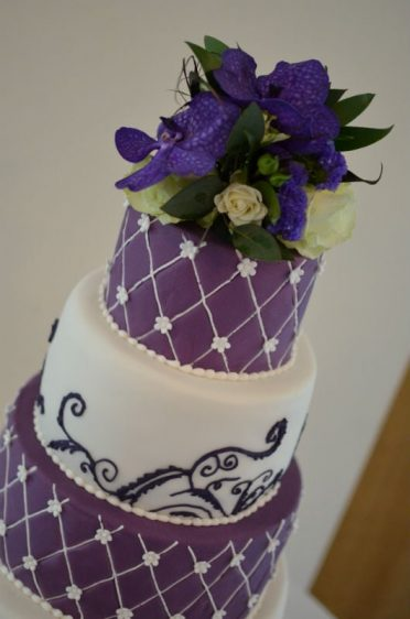 Close up of purple piped wedding cake.