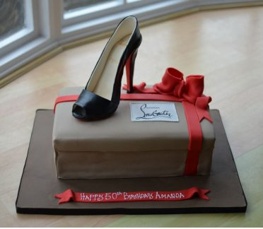 Sugar Louboutin shoe cake with red bow.
