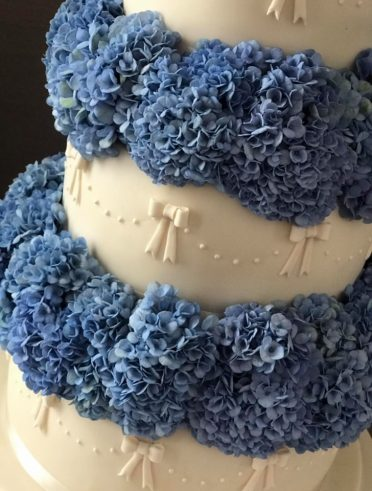 Close up of Ivory Bows & blue hydrangea wedding cake at Carlton Hotel Bournemouth