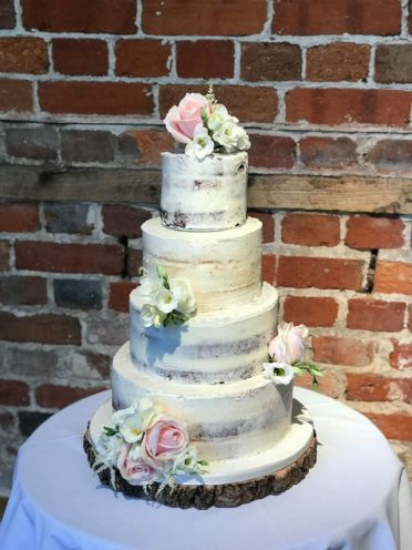 Semi-Naked wedding cake at Highcliffe Castle. Flowers by Simply Flower