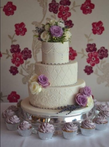Pretty three tier with fresh flowers and cupcakes at The Cottonwood