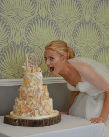 Playful bride with her wedding cake.