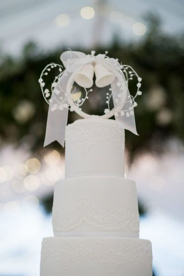 Close up of the top tiers of the 5 tier white lace wedding cake.
