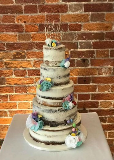 Five tier semi-naked wedding cake at Sopley Mill. Decorated with brides own accessories.