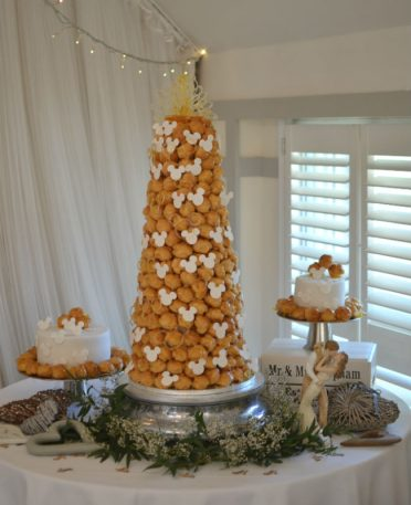 Minnie Mouse croquembouche with separate wedding cakes to match. The Kings Hotel