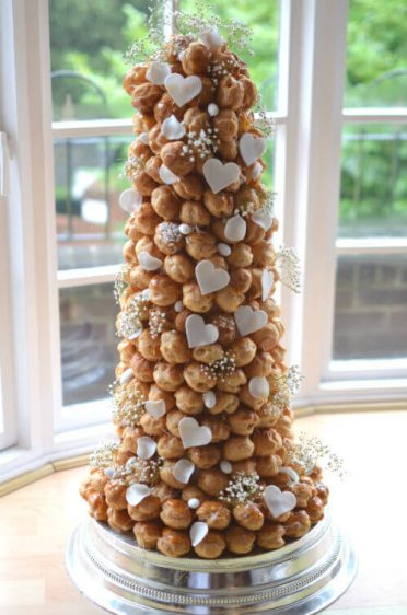 Croquembouche with white hearts, petals,almonds and gypsophila.